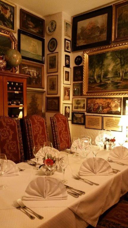 eine eingedeckte Tafel mit schön gefalteten Stoffservietten, Gläsern und Silberbesteck daran steht französische Bestuhlung und im Hintergrund eine große Gemäldewand und ein edler Holzweinschrank
